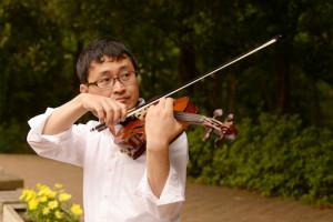 公園のベンチに腰掛けて、バイオリンを弾くいちろーたの写真